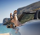 picture of shale  - female legs dangling from the open car window in the shales Stock Photo - JPG