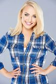 Smiling confident young blond woman posing in a blue checked shirt with her hands on her hips and a