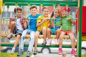 stock photo of swing  - Cheerful kids sitting on swing and looking at camera - JPG