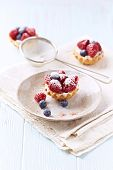 stock photo of tarts  - Little Mascarpone Tarts with Raspberries and Blueberries - JPG