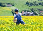 stock photo of dungarees  - A Baby Girl In Dungarees With A Soft Toy In Her Hands Walking In The Field Full Of Buttercups With The Farms On The Background - JPG