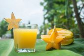 Starfruit and juice on a banana leaf.