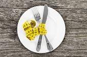 Plate With A Knife And Fork Wrapped In Measuring Tape On A Wooden Background. Diet Concept