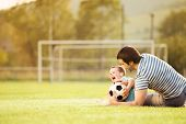 pic of football pitch  - Young father with his little son playing football on football pitch - JPG
