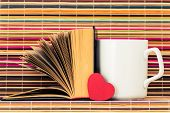 picture of memory stick  - The white cup the opened book and red heart before them on a color background from bamboo sticks - JPG