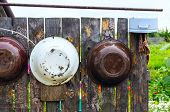 Metal Bowls Hanging On A Wooden Fence