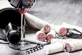 Corks, corkscrew, wine glass and bottle on a wooden  background