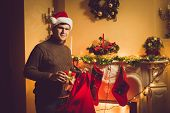 Toned Photo Of Smiling Man Taking Gift Box Out Of Red Santa Bag