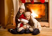 Smiling Girls In Sweater And Hats Warming Up At Fireplace At Christmas