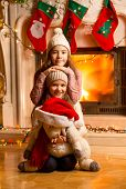 Two Smiling Girls Sitting Next To Fireplace At Christmas Eve