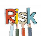 Multiethnic Group of Hands Holding Word Risk