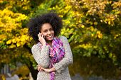 Smiling Young Woman Calling By Mobile Phone Outdoors