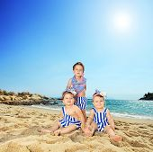 Three cute little toddlers sitting on a tropical beach shot with a tilt and shift lens