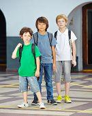 Three children in a row in elementary school on a schoolyard