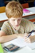 Lefthanded boy writing in elementary school class with a pencil