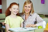 Happy teacher giving smiling girl private lessons after school