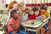 Children at laptop computer in elementary school with teacher