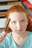 Girl in class thinking with pencil on her forehead in elementary school