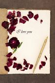 Old fashioned vintage hemp notebook, I love you phrase, ink pen and red rose with petals over lokta paper background.