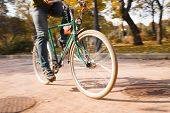 Close-up of young man riding bicycle in park
