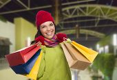 Pretty Warmly Dressed Mixed Race Woman In Outdoor Mall with Shopping Bags.