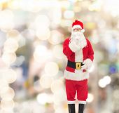 christmas, holidays and people concept - man in costume of santa claus making hush gesture over lights background