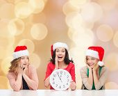 christmas, winter, holidays, time and people concept - smiling women in santa helper hats with clock over beige lights background