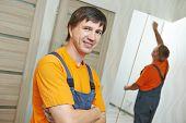 Male carpenter worker portrait in front of coworker prepairing internal door for installation