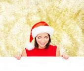 christmas, x-mas, people, advertisement and sale concept - happy woman in santa helper hat with blank white board over yellow lights background