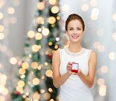 winter holidays, presents and people concept - smiling woman in white dress holding red gift box with diamond ring over christmas tree lights background