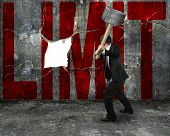 Businessman Holding Sledgehammer Hitting Red Limit Word On Concrete Wall