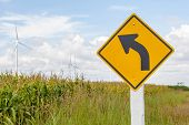 Curved Road Traffic Sign With Windmill Background In Wind Farm.