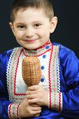 pic of idiophone  - Little smiling boy playing maracas against dark background - JPG