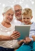 family, generation, technology and people concept - smiling grandparents and grandson with tablet pc computer at home