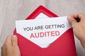 stock photo of financial audit  - Cropped image of hand holding You Are Getting Audited card in envelope - JPG