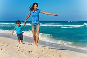Happy mother with son holding arms and running