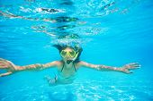 Woman wearing snorkeling mask swimming underwater