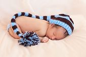 Newborn In Knitted Hat On Beige Background