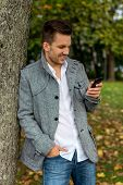 a man writes a text message on his cell phone. communication with a smart phone