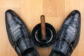 Classic Men's Shoes, Ashtray And  Fuming Cigar On The Wooden Floor