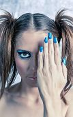 Beautiful model with pigtails, fancy makeup and blue manicure