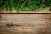 Pine Tree Border With Red Garland On Old Wooden Background