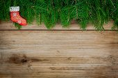 Pine Tree Border With Red Sock On Old Wooden Background
