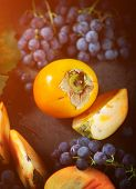 Persimmon And Grapes Still Life.autumn Season Food Photo. Yellow Toning Applied