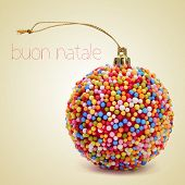 a christmas ball coated with nonpareils of different colors and the sentence buon natale, merry christmas written in italian, on a beige background