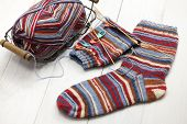 knitting winter warm socks, yarn ball and knitting needles, handmade christmas present