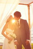 Sunset Wedding. Bride and Groom Kissing at Sunset. Romantic Married Couple.