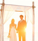 Beautiful Sunset Wedding by the Sea. Bride and Groom at Sunset on Wedding Day