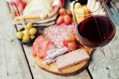 stock photo of charcuterie  - Glass of red wine with charcuterie assortment on the background