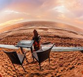 table and chairs on a tropical beach with sunset views. Fish-eye lense view